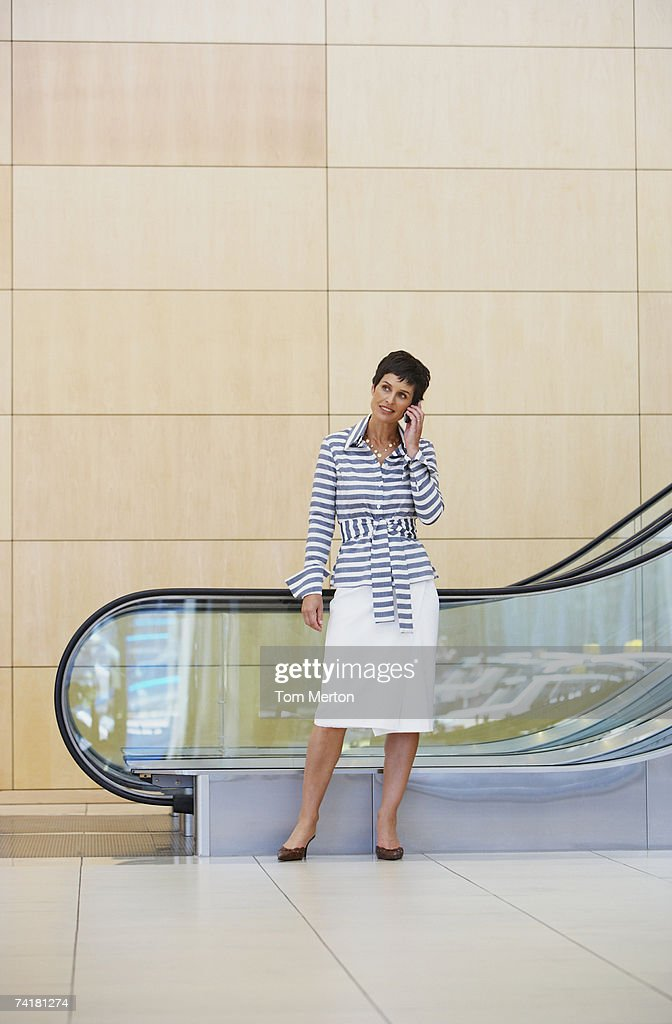 Woman on cell phone with escalator in background : Stock Photo