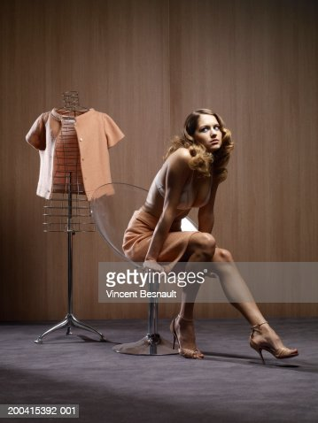 Woman on chair by jacket on dressmaker's model : Foto de stock