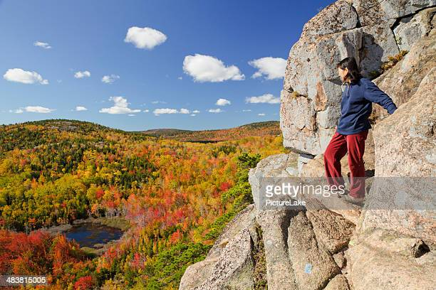 Woman on cliff, Acadia National Park, in Autumn