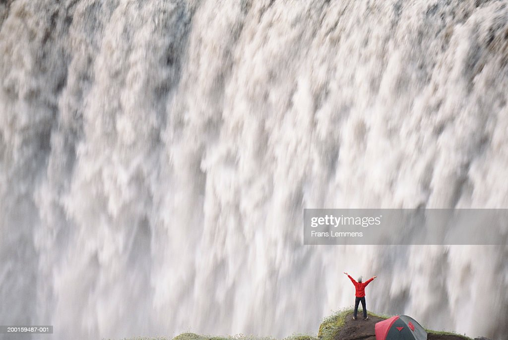 Woman on cliff edge by waterfall, arms outstretched, rear view : Stock Photo
