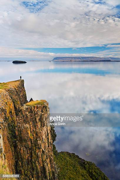 Woman on cliffs overlooking calm harbor, Iceland