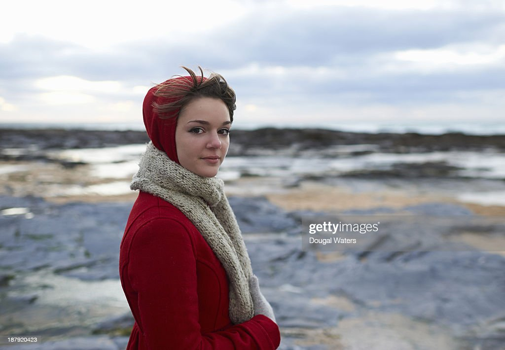 Woman on coastline in red coat. : Stock Photo