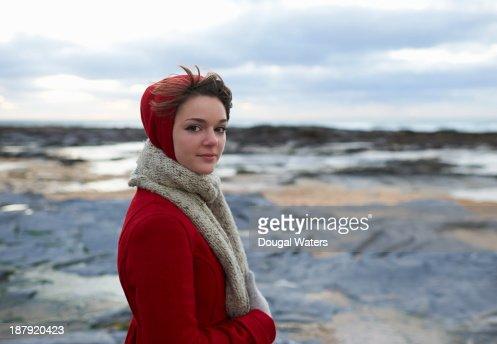 Woman on coastline in red coat. : Stock Photo