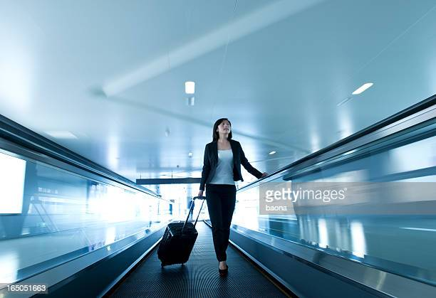 Woman on conveyor pulling trolley suitcase