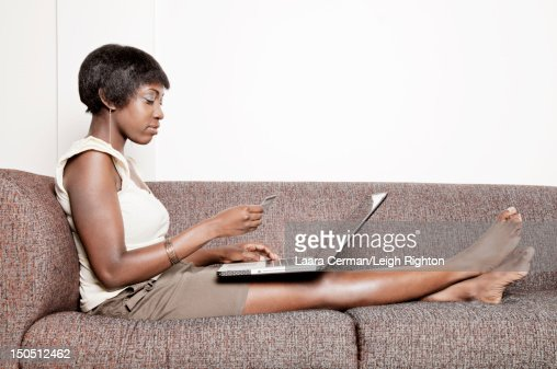 Woman on couch online shopping. : ストックフォト
