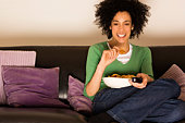 Woman on couch with remote control and popcorn