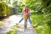Woman On Cycle Ride In Countryside Smiling At Camera