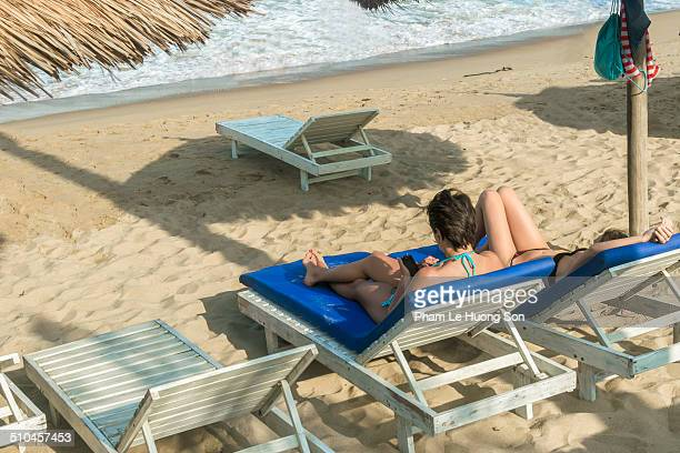 woman on deckchair enjoying music from smart phone