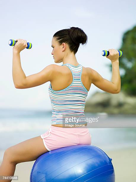 Woman on exercise ball using dumbbells