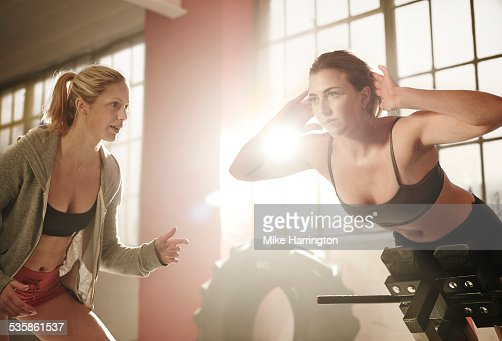 Woman on extension bench in industrial gym
