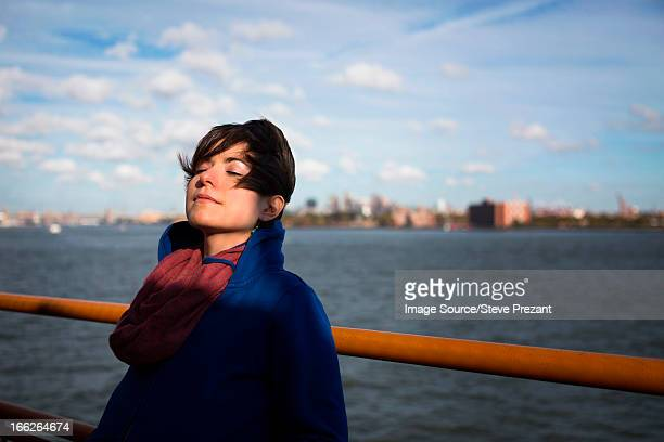 Woman on ferry in urban harbor