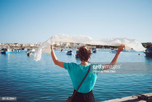 Woman on fishing port with foulard on the wind