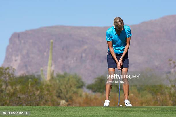 Woman on golf course, putting