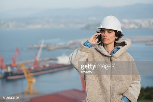 woman on harbor with safety helmet talking on the phone : Stock Photo