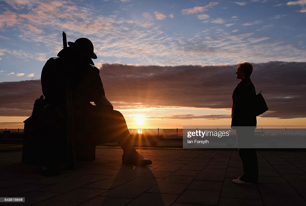 A woman on her way to work pauses at dawn to look at the World War One statue of 'Tommy' on June 29, 2016 in Seaham, England. The statue created by artist Ray Lonsdale to commemorate the armistice is officially entitled 1101, stands 9ft 5in tall, weighs 1.2 tonnes and is built from corteen steel. It represents a World War One soldier who sits with head bowed reflecting on the horrors of the war in the first minute after peace was declared in 1918. The sculpture is also intended to represent Post Traumatic Stress Disorder which many of the returning soldiers endured. This Friday (July 1) marks the anniversary of the start of the Battle of the Somme during World War One which was the largest battle of the war on the Western Front with over a million men wounded or killed. It was one of the bloodiest battles in human history.
