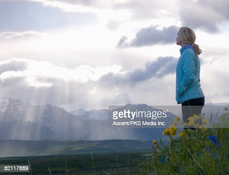 Woman on hillside of flowers, looking at sun rays and distant mountains : Stock Photo