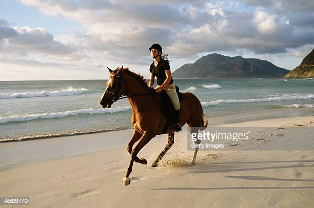 Woman on horseback riding on beach