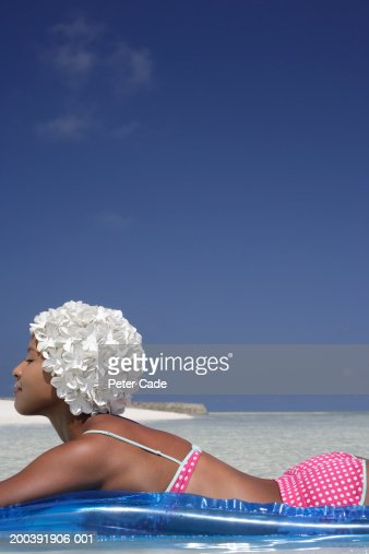 Woman on inflatable raft in sea, wearing white bath hat, side view