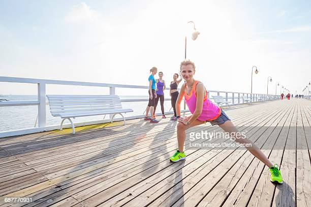 Woman on jetty doing stretching exercise