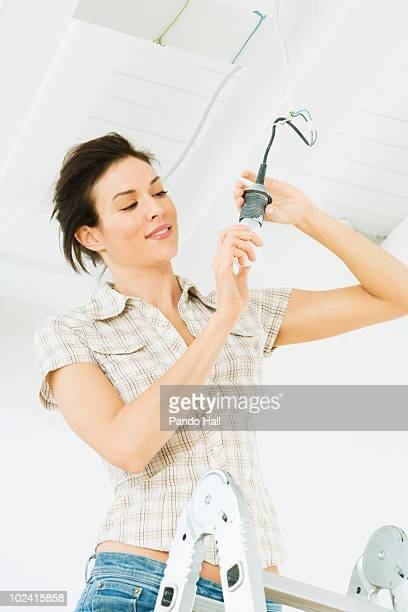 Woman on ladder changing light bulb, smiling