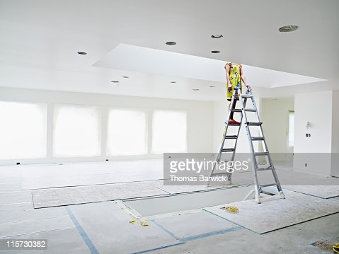 Woman on ladder in home looking into skylight : Stock Photo