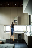 woman on ladder looking in cabinet