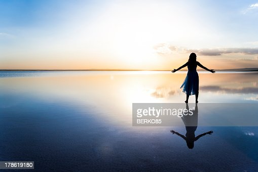 Woman on lake at sunset representing freedom : Stock Photo