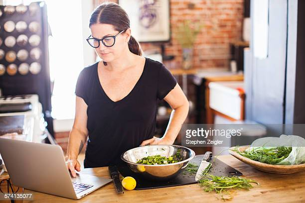 Woman on laptop computer in her home kitchen