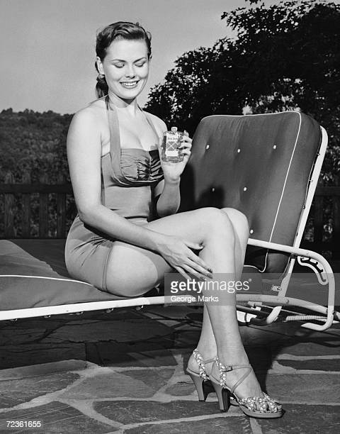 Woman on lawn chair applying oil to her legs