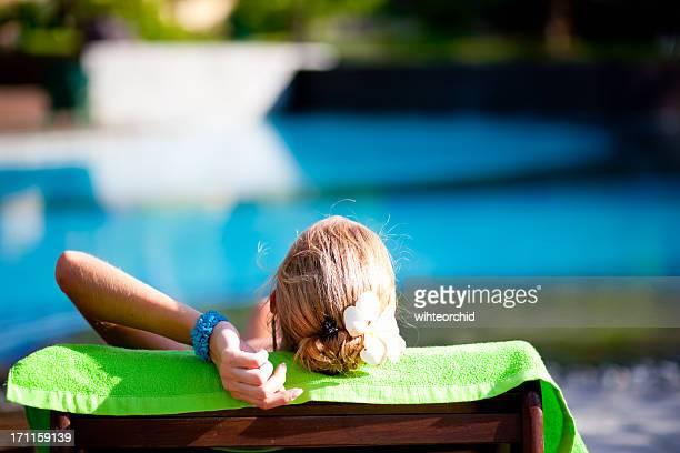 Donna sulla sedia su prato nei pressi di una piscina