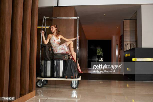 Woman on luggage trolley being pushed