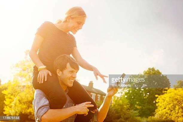 Woman on man's shoulders, looking at smart phone.