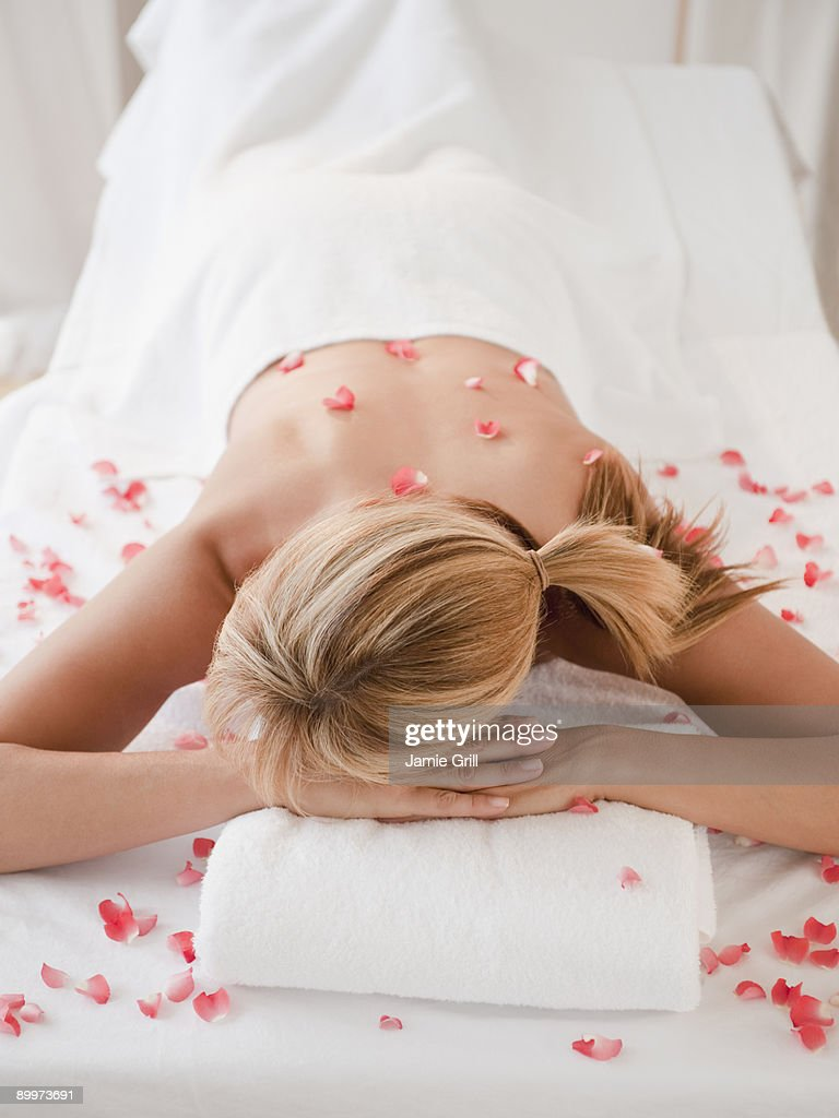 Woman on massage table with flower petals : Stock Photo