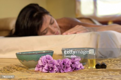 Woman on mattress with aromatherapy objects