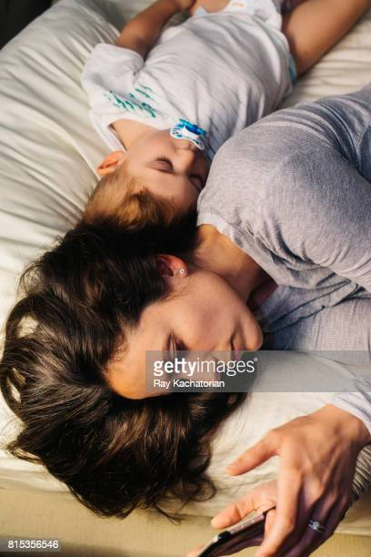 Woman on mobile device with toddler sleeping