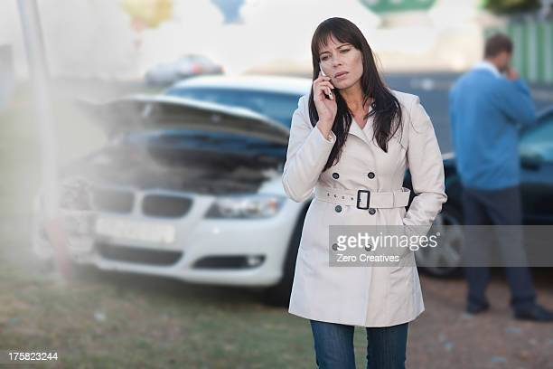 Woman on mobile phone after car accident