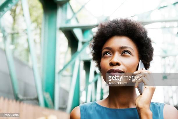 Woman on mobile with iron grid bridge
