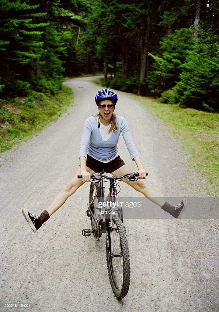 Woman on mountain bike, legs apart : Stock Photo