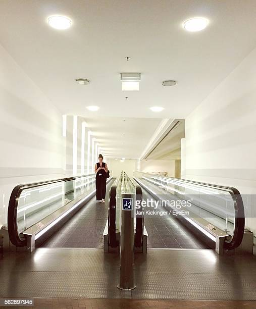 Woman On Moving Walkway In Building