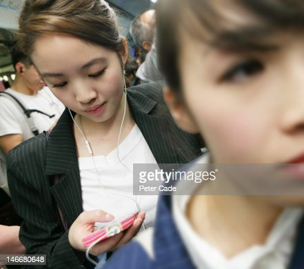 woman on MTR listening to music on phone : Stock Photo