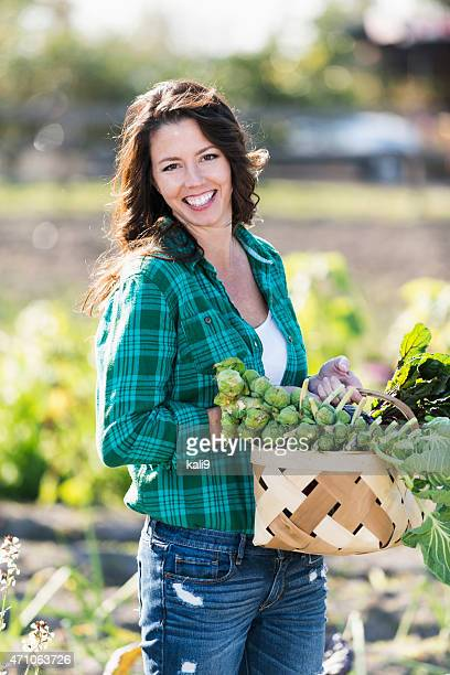 Femme dans la ferme biologique porter Panier de légumes