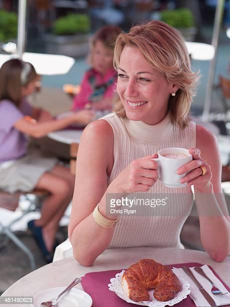 Femme sur une terrasse extérieure avec un café et un croissant