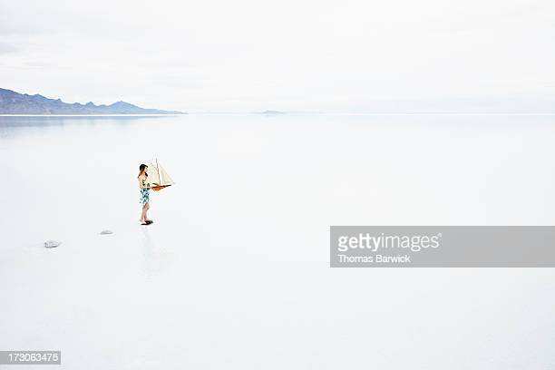 Woman on path in lake holding model sailboat
