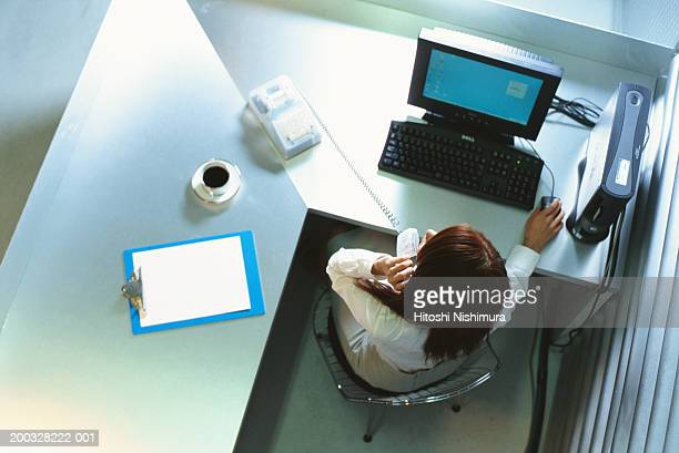 Woman on phone at office desk, overhead view