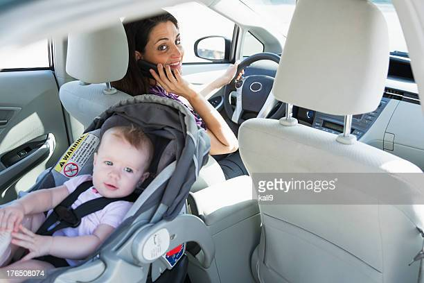 Woman on phone driving with baby