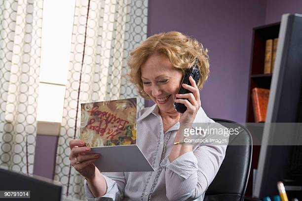 woman on phone looking at christmas card