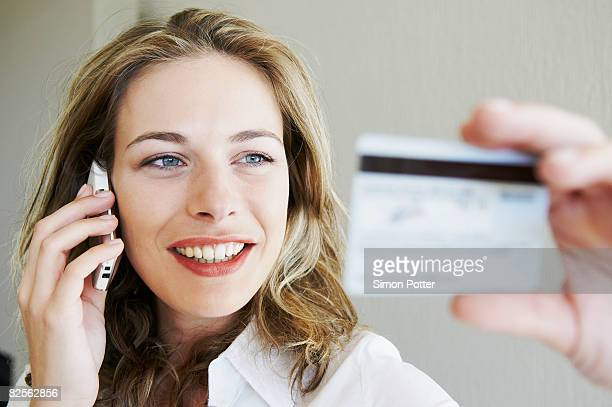 Woman on phone, looking at credit card