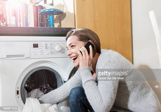Woman on phone while filling washingmachine.