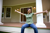 New home owner sitting on porch of suburban home with arms outstretched, showing it off