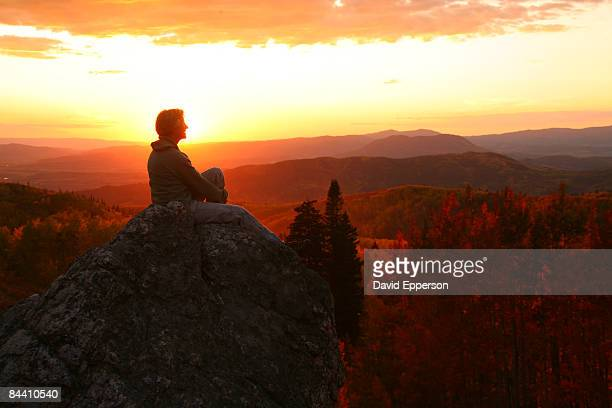Woman on rock at sunset in Colorado